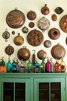 vintage copper pans and molds above antique soda-water bottles