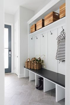 Lovely black and white mudroom features gray herringbone pattern floor tiles placed beneath a a white built-in bench fitted with a black top.