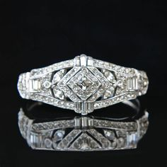 Sparkling clear rhinestones and geometric designs are hallmarks of the Art Deco style, and this gorgeous bracelet certainly has them with its combination of round and baguette stones and center medall