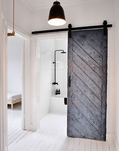 This sliding barn door looks incredible in a fresh and clean white bathroom. Via April and May.