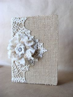 This lovely journal is covered in burlap with a bit of vintage crochet wrapped around the spine. The handmade fabric flower has bits of lace, tulle and burlap tucked into it with a vintage looking button in the center. This is a sturdy hardback book, the pages are brown lined paper. Book is 6 by 8 inches.  56 pages.