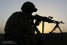 A Paratrooper from the 3rd Battalion the Parachute Regiment (3 Para) is silhouetted against the setting sun as he provides cover for a convoy of vehices during Operation Oqab Tsuka in Afghanistan.