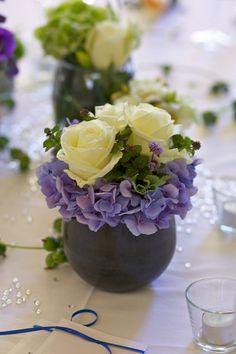 Schöne Tischdeko mit Rosen und Hortensien in kleinen Vasen.