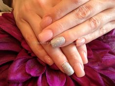 Acrylic nails with pink whisper gel polish  and silver glitter gel polish on ring finger