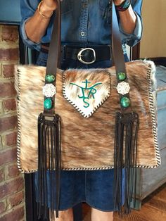 The custom cowhide Buckaroo Diaper Tote. The customers brand is in turquoise suede, the straps have Swarovski crystal conchos, turquoise stones and hand cut fringe. There are exterior pockets on the sides to hold a baby bottle or a cell phone.  gowestdesigns.us