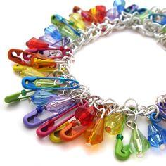 Kierrätä hakaneulat käsi- tai kaulakoruissa. Lisää väriä saat esimerkiksi lakkaamalla hakaneulat kynsilakalla. Rainbow coloured safety pins used in a easy DIY recycled bracelet.