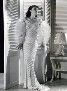 Strictly Dynamite (1934) - Lupe Velez as Vera wearing an off-shoulder dress with beaded herringbone motif and tulle ruffled sleeves.  The costumes were designed by Walter Plunkett.