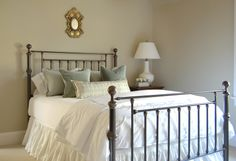 wrought iron bed, romantic ruffled white bedding, greige walls...