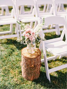 Wood stump with mason jar floral centerpiece on it for aisle decor.