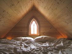 love the church window in the attic space turned comfy sleeping loft area
