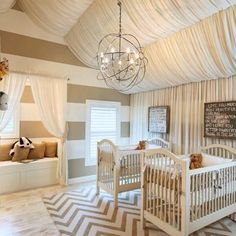 Glamorous, Gender Neutral Nursery for twins with stripe walls, a fabric canopy and wall covering and chevron rug