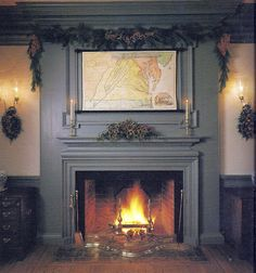 This inviting hearth at Craft House is decorated in the traditional Williamsburg manner. The colorful mantel arrangement of lady apples, arborvitae, English ivy, variegated holly foliage, and sprigs of bright holly berries; thick pine roping punctuated with variegated holly and large sprays of red nandina berries at the corners; and coordinated plaques of lady apples and greens hanging from the sconces