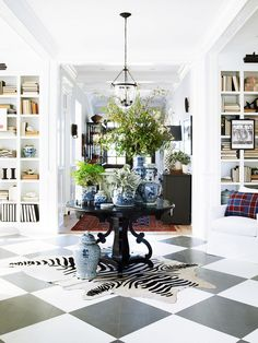 Airy coastal entryway with zebra print hide and surrounding built-in bookshelves.