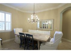 Shabby Chic formal dining room with white slip covers and crystal chandelier.  Il Regalo | North Naples, Florida