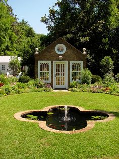 Potting shead with a formal style, weathered bricks, and custom windows adds elegance to the property, sits on an oval garden with a quatrefoil fountain.