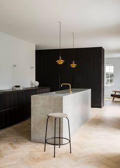 Küche dunkles Holz schwarz Kücheninsel Küchenblock grau Beton Barhocker Leuchte gold weiß Fischgrätparkett skandinavisch modern minimalistisch schlicht einrichten wohnen Interior Design Küchenschränke Interieur Innenarchitektur Wohninspiration Wohnidee Norm Architects
