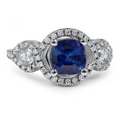 This illustrious halo ring features a remarkable cushion cut sapphire outlined in shimmering diamond pavé accents. Pear-shaped bezel set diamonds sit on the shoulders for a graceful effect.