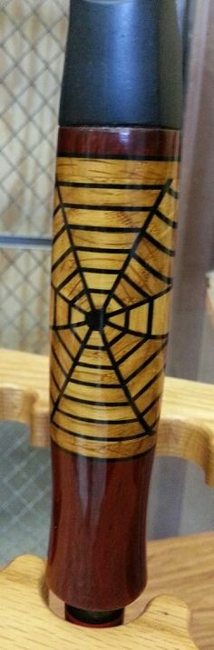 This is a spider web design fishing rod handle made out of wood, pieced together and turned on a lathe by Mark Blabaum.  It is incredible!