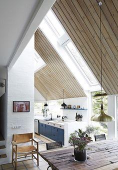 """Wow! Träet i det resliga innertaket gör den enorma höjden extra påtaglig. Glaspartierna tar ingen hänsyn till om väggen övergår i tak eller i en annan vägg. Det är hela utkarvade öppningar för att ge ljus och utblickar precis där man vill. Resultatet utvändigt är väldigt modernt. Byggnaden är en abstrakt volym som vilar på en tung, murad hjärtvägg som """"landar"""" på stengolvet mitt i huset"""