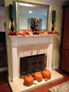 Travertine fireplace with white mantle decorated for autumn.