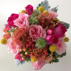 Bright pin cushion protea, succulents, garden roses, hypericum berries, billy balls and  dusty miller make this unique bouquet one of our favorites!