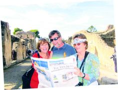 Kathy Staley, Paul Staley, and Pam Garrison sharing The Taos News in the ruins of Herculaneum near Naples, Italy.
