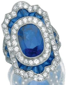 Sapphire and diamond ring,    circa 1920. Centring on an oval sapphire within a shield-shaped mount set with calibré-cut sapphires, single- and circular-cut diamonds. Sotheby's.
