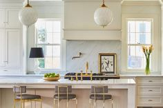 Cream kitchen features cream cabinets paired with white marble countertops and backsplash.