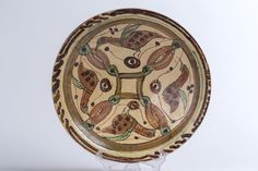 A Sari plate with four birds Iran, XI secolo Earthenware with clear slip and decorated with coloured splips