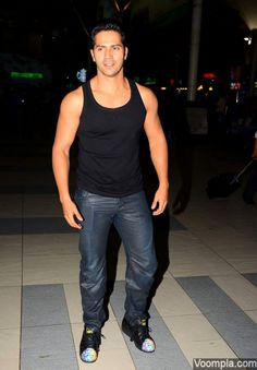 Varun Dhawan styles up his airport look in a black vest, shiny jeans and adidas sneakers. via Voompla.com