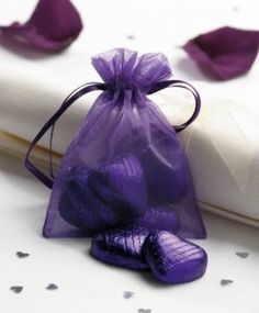 Purple chocolate hearts wedding favors with sign LOVE IS SWEET.