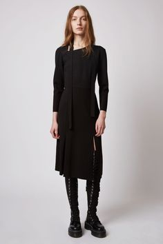 A long sleeved dress with a feminine neck tie and cut out feature. The skirt features a decorative split with a longer, gently curved asymmetric hem at the front. Dagmar