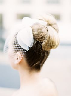 Bridal bun + bow + birdcage veil :: Such a pretty style for a retro or Rockabilly Wedding:: Bridal Hairstyle:: Up Dos:: Bird Cages and Buns