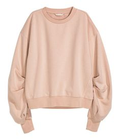 Powder beige. Wide-cut sweatshirt with dropped shoulders, long sleeves, and ribbing at cuffs and hem. Soft, brushed inside.