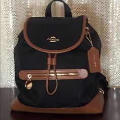 """NWT Coach Sawyer Backpack Black/Saddle PRICE FIRM AND FAIR  You can also find me on Ⓜ️ecarℹ️ #F37240 MSRP: $325 Twill Canvas (WATER RESISTANT) w/ leather trim Black w/ saddle leather trim 12.75"""" H x 11.25"""" L x 4.25"""" W Black fabric lining Magnetic front flap closure Leather drawstring closure Front zip pocket Two interior open pockets / one zip pocket  Adjustable back straps Light weight only 1lb 3oz empty Coach Bags Backpacks"""