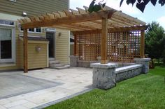 Pergola incorporates a bench wall that  extends beyond the patio.
