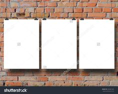 Close-up of three hanged paper sheet frames with clips on brick wall background