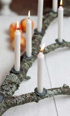 Mossy branch with white candles could be so pretty.