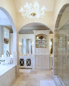 Traditional white and ivory bathroom with dual vanities and a large glass shower