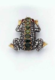 A GREEN GROSSULAR GARNET AND DIAMOND FROG BROOCH  The pavé-set diamond body with demantoid garnet back and ruby eyes, mounted in silver and gold