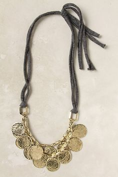 DETAILS  A bib of hammered gold coins jingle-jangles around your neck instead of in your pocket
