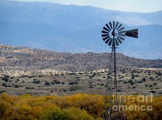 A tall windmill looms above the Arizona landscape of hills and mountains, with yellow aspen trees in the foreground. Buy prints at eva-kato.artistwebsites.com