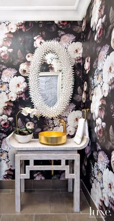 In the small powder room, Ellie Cashman Design's floral wallpaper makes a big impact. Equally bold elements also stand out, including Maestrobath's Pert Rho Lux gold-leaf sink atop a custom altar table featuring a gilded-gesso finish. The white mirror is by Barry Dixon for Arteriors.