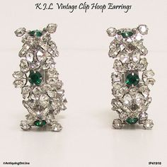 Vintage KJL Earrings, Kenneth Jay Lane 1960s to 1970s Emerald Green and Clear Rhinestone Clip On Earrings  Each of these fabulous rare K.J.L. rhodium plated clip on hoop earrings has four chaton cut emerald green centers surrounded by clear crystal rhinestones in a layered floral design. All stones pronged in.  These vintage KJL (Kenneth Jay Lane) earrings are signed K.J.L. on an applied oval plaque on the inside of each earring, the signature used in the 1960s and 1970s. Signed plaque…