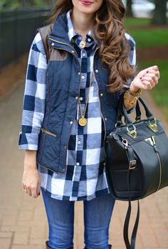 Buffalo plaid button up, navy puffer vest, skinny jeans, & black bag.