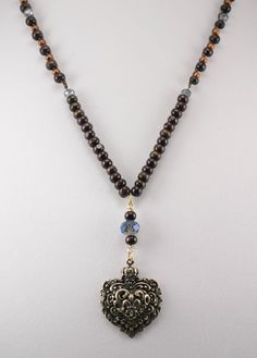 Wooden beads with sky blue crystals, copper seed bead crochet with brown thread and a heart vintage pendant. $53.00