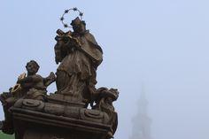Rzeźba św. Jana Nepomucena na Starym Rynku. W tle wieża ratuszowa.