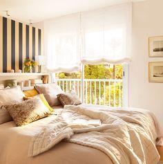 Dormitorio con ropa de cama en beige y dorado y estores blancos a las ventanas