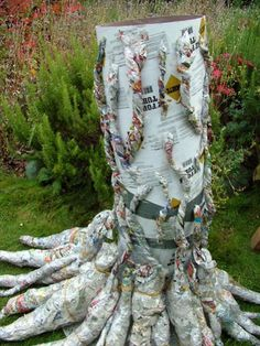 make a haunted tree - Twisted pieces of newspaper are taped to the trunk for texture.  This will then all be covered with the 1 mil plastic.