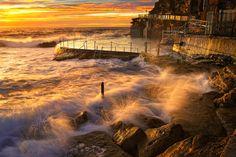 Breathtaking photograph of waves crashing on the shore at sunset.